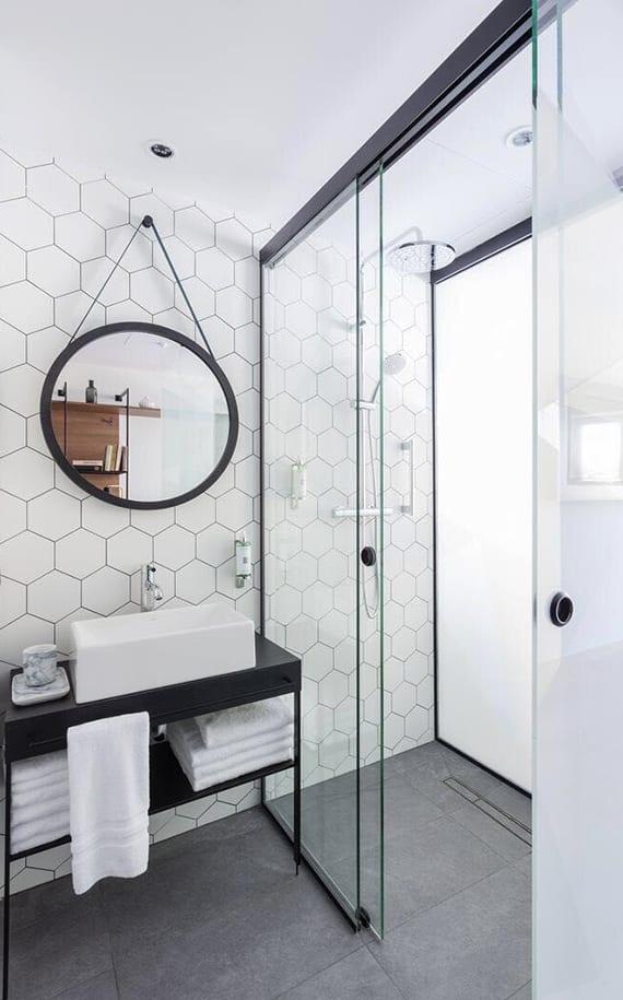 moderne badezimmergestaltung im industrial stil mit schiebeglastüren, weißen hexagon fliesen, schwarzem waschtischschrank und rundem wandspiegel im schwarzen spiegelrahmen