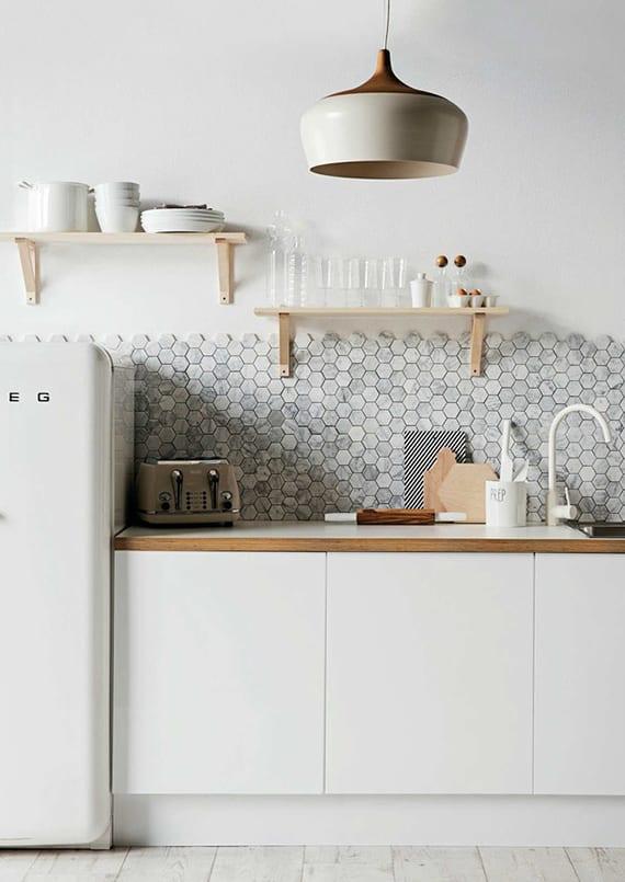 moderne wandgestaltung küche mit spritzwand aus hexagon-mosaik in weißgrau und holzwandregalen_moderne küche weiß mit weißen küchenschränken, weißer mischbaterie und retro kühlschrank weiß