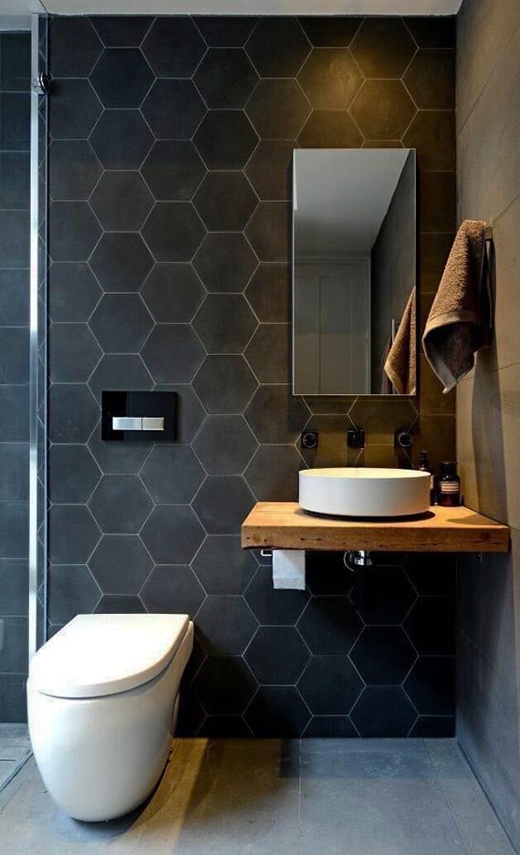 coole gestaltungsidee für modernes badezimmer in schwarz mit schwarzen hexagon fliesen und kleinem rustikalen waschtisch aus holz mit rundem waschbecken und schwarzen armaturen