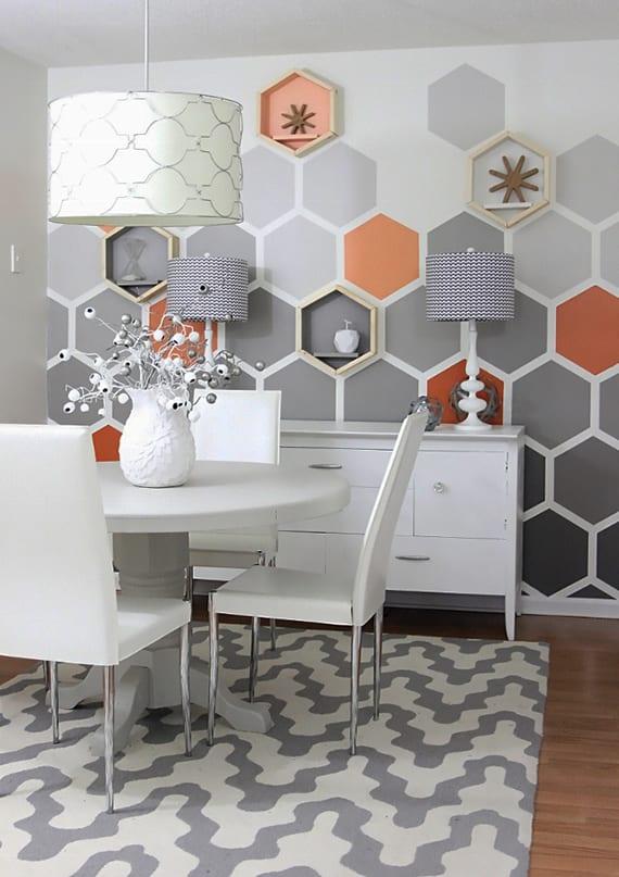 kreative raumgestaltung und farbgestaltung wohnzimmer mit hexagon wandmuster in hellgrau, dunkelgrau und orange, sideboard weiß, esstisch rund und esszimmerstühlen in weiß