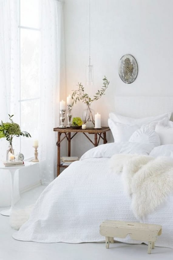 gemütliche schlafzimmer gestaltung in weiß mit weißer pelzdecke, beistelltisch rund und nachttisch aus holz mit silbernen kerzenhaltern und grünen pflanzen