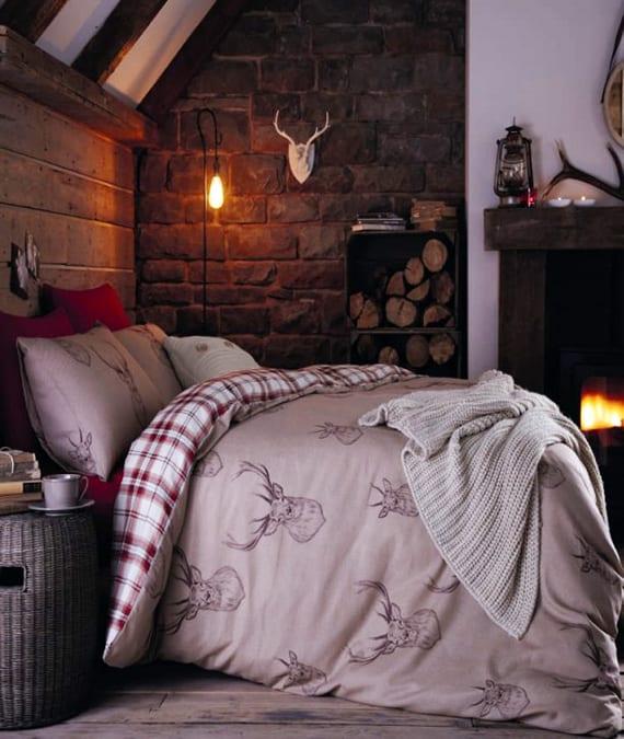 schlafzimmer gestalten mit kamin, mauerwand, holzbettkopfteil und weihnachtlicher bettwäsche mit hirsch-motiv und rot-weißem karomuster
