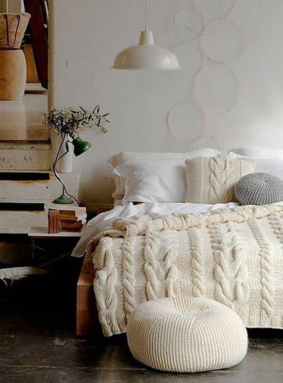 weißes schlafzimmer gemütlich einrichten mit massivholzbett, grüner tischlampe, weißer strickdecke und strickpuffen