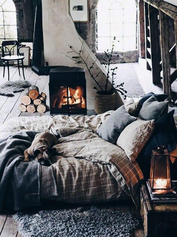 rustikales schlafzimmer gemütlich einrichten mit kamin, holzkiste-nachttisch mit laterne, grauem schafspelz teppich und karierter bettwäsche beige
