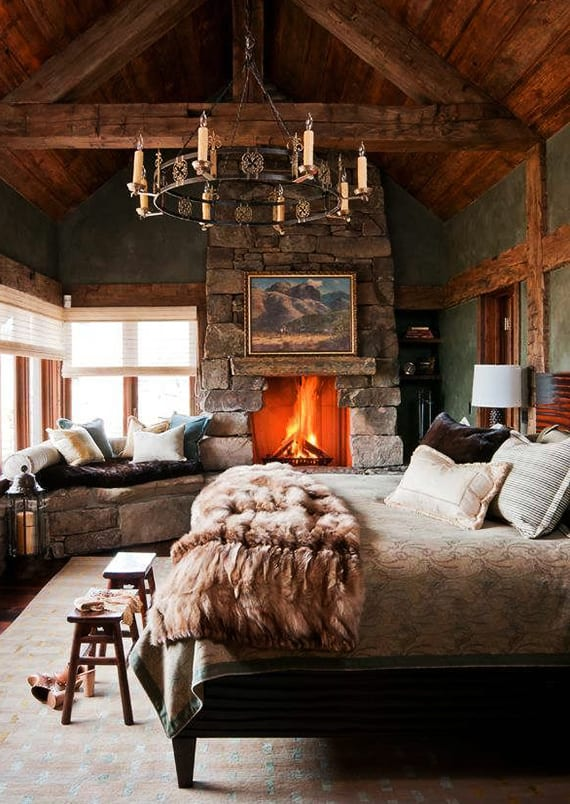 rustikale schlafzimmer mit kamin und fensterbank aus steinen, wandfarbe grün, holzhocker,vintage-kronenleuchter