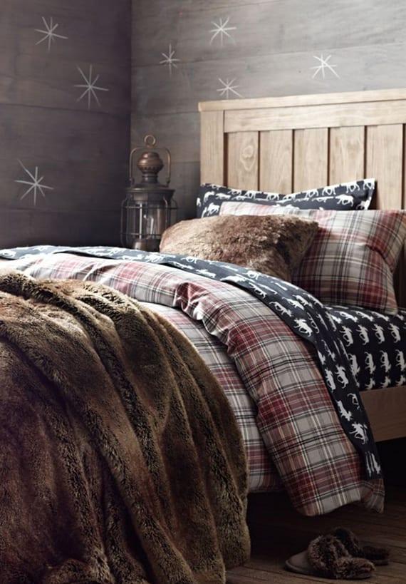 rustikales schlafzimmer design mit holzwandverkleidung, schneeflocken-wandmuster, vintage laterne und dunkelblauer bettwäsche mit hirsch-muster