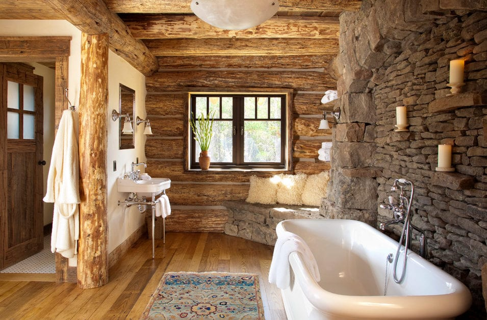 traumhaftes badezimmr im landhausstil mit echtem holzfußboden, eck-sitzecke aus steinen, waschbecken mit metallbeinen, wand und decke aus rundholz und romantische wanddeko mit kerzen