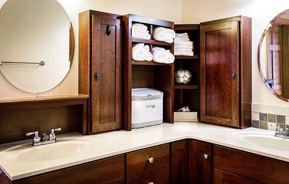 gemütliches badezimmer im landhausstil mit badezimmermöbel und eckwaschtischschrank aus dunklem holz und weißer waschtischplatte mit ovalen waschbecken_ aufbewahrungsideen fürs bad