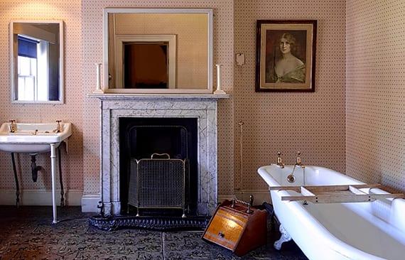 einrichtungsideen für badezimmer im landhausstil mit Kaminsims aus marmor, klasischer badewanne freistehend, tapeten mit punktmuster, keramik waschbecken mit beinen und rustikaler wanddeko mit spigeln und bildern