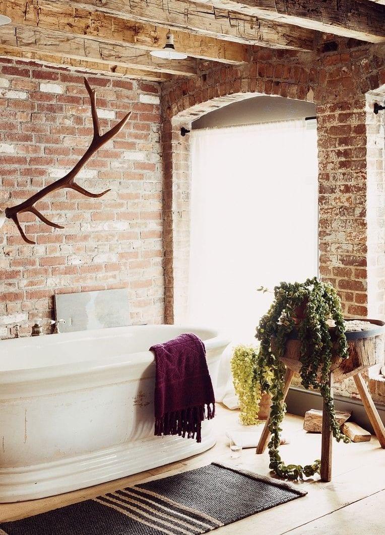 badezimmer im landhausstil mit wänden aus ziegel, bogenfenstern, badewanne freistehend, schwarzem vorleger und landhaus dekoration mit Geweih, rundem holzhocker, holzeimer und grünen pflanzen
