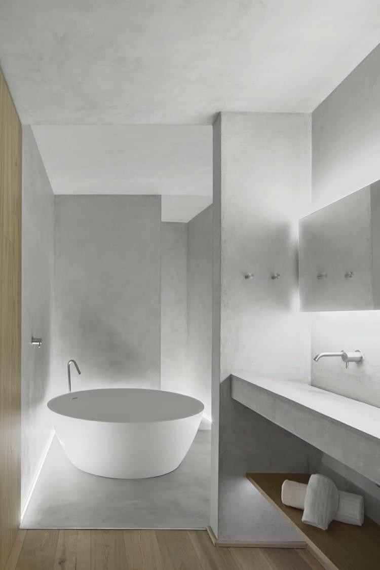 moderne raumgestaltung kleiner bäder mit waschbecken und Wände aus Beton, indirekter bodenbeleuchtung, runder badewanne und holzregal für tücher