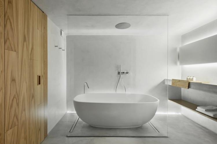 raumgestaltungsidee für modernes badezimmer mit Deckenbrausen, freistehender badewanne, glastrennwand, betonwaschbecken und indirekter beleuchtung am boden und hinter dem badspiegel