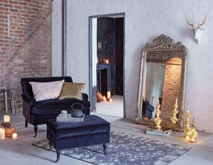 zuhause neu gestalten zur weihnachtszeit mit deko-hirschkopf weiß, großem Spiegel ind Silberrahmen, klasischem Armsessel und Hocker in blauem Samt und Ziegel-Tapete