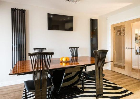 moderne wandgestaltung esszimmer mit vertikalen wandheizkürpern_kleines wohnesszimmer gestalten mit zebra-teppich, modernem esstisch schwarz und esstischstühlen in chrom
