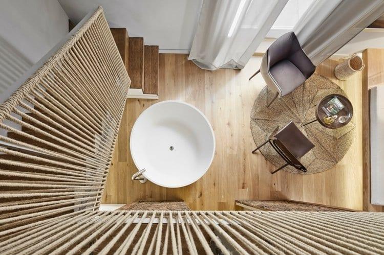 originelle gestaltungsideen für moderne raumgestaltung einer Mezzanin-Wohnung mit freistender badewanne im wohnzimmer mit eichenholzboden, rundem Bastteppich und couchtisch, hellgrauen gardinen und designer stühlen in dunkelbraun