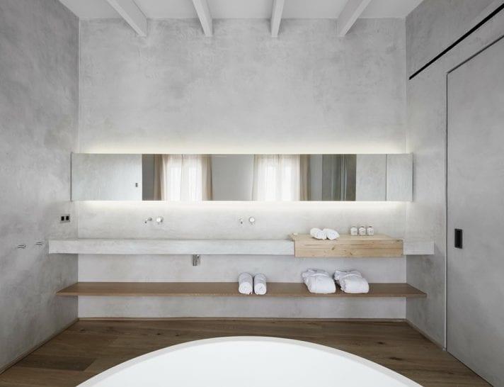 idee für modernes badezimmer mit minimalistischem interieur_moderne raumgestaltung im bad mit betonwände, betontür, betonwaschbecken und LED-hinterleuchtetem Wandspiegel