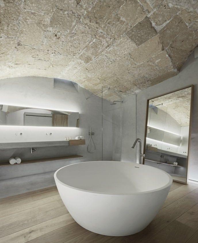 modernes badezimmer mit holzfüßboden, ruder badewanne und dusche mit glaswand, großem Spiegel und länglichem Wandspiegel mit indirekter beleuchtung, bogendecke aus naturstein