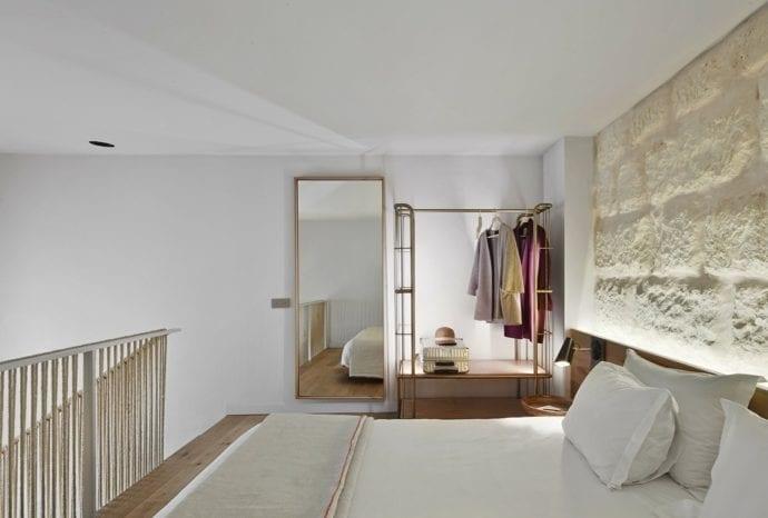 moderne schlafzimmergestaltung mit akzentwand aus kalkstein, holzbett mit holzkopfteil und indirekter wandbeleuchtung, kleiderständer und Spiegelrahmen aus bronze und hafseil-geländer