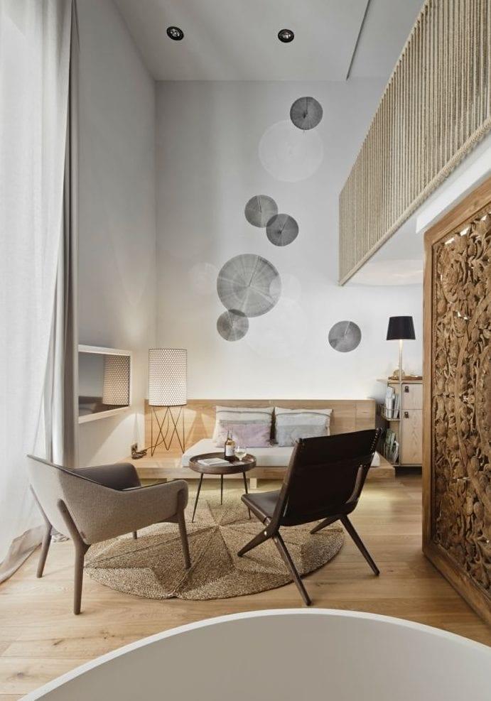 kleines wohnzimmer modern gestalten mit Holzbank-Sofa mit Polsterkissen, Holztür mit Mandala-Schnitzerei, rundem Bastteppich unter rundem Kaffeetisch, Hanfseil-Geländer und holzabdrücke-wanddeko