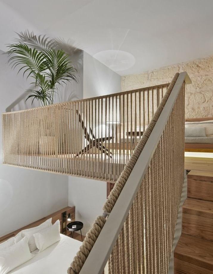 moderne mezzanin-raumgestaltung mit hanfseil-geländer, holzinnentreppe, kalksteinwand und holzbett mit kopfteil
