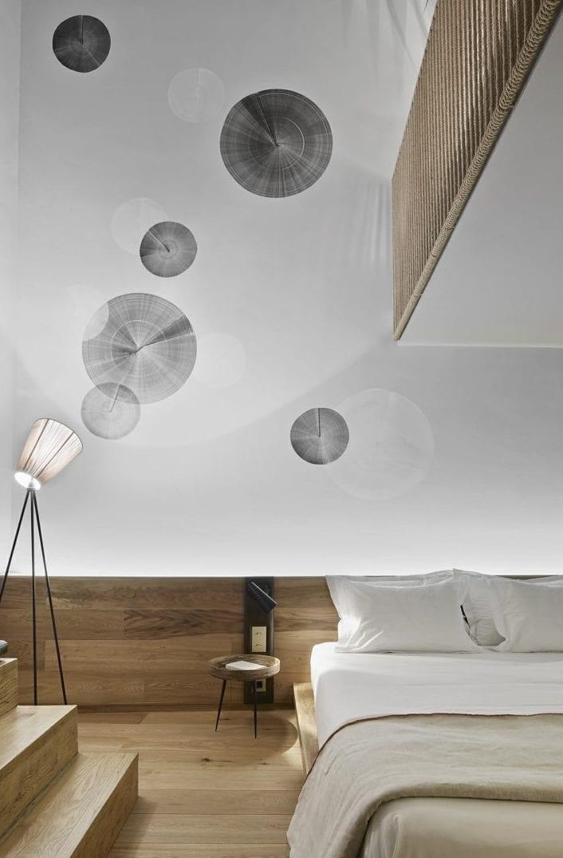 coole wandgestaltung schlafzimmer und moderne schlafzimmergestaltung mit holzwandverkleidung als bettkopfteil mit eingebauten Nachttischlampen und kleinen runden beistelltischen