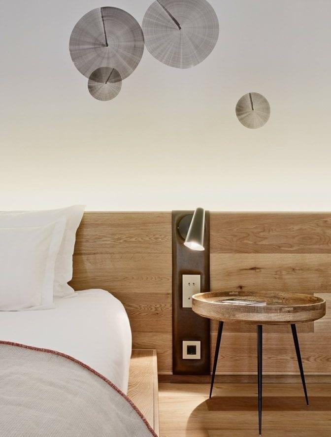 modernes schlafzimmer mit niedrigem holzbett, holzkopfteil mit brauner wandleuchte, rundem beistelltisch holz und kreative wanddeko mit holzabdrücken