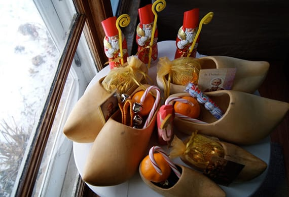 weihnachtliche Dekoration zum Nikolaustag mit Zitrusfrüchten und Süßigkeiten in Holzschuhen