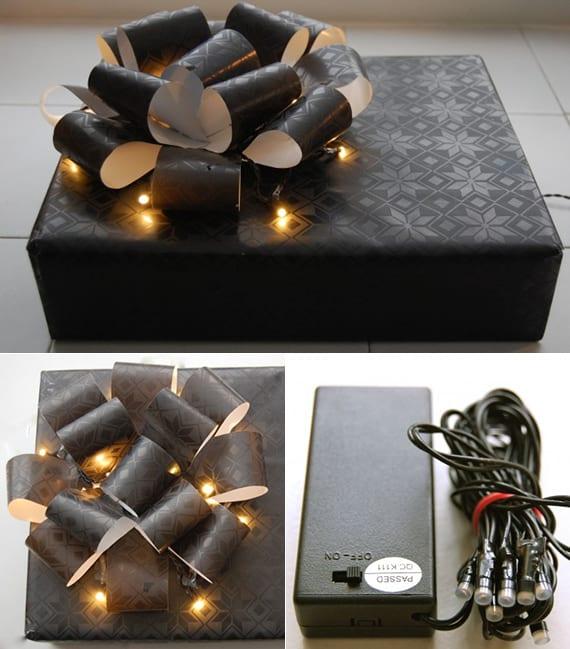 originelle Geschenkverpackung mit schwarzem Geschenkpapier, Geschenkschleife und Lichterkette für Weihnachtsgeschenke