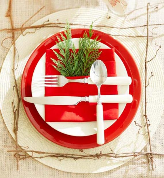 tisch weihnachtlich decken mit weißen und roten tellern, Tafelsilber und Immergrün in roter Bestecktasche-Serviette