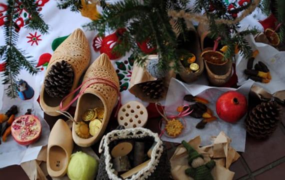 weihnachts dekoidee mit holzschuhen, großen nadelbäume zapfen, granatäpfeln und schokoladenen Münzen