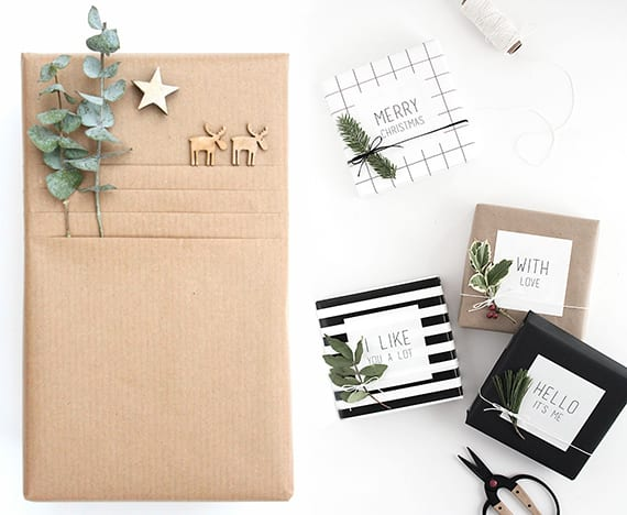 geschenke verpacken weihnachten mit grünen zweigschnitten, hirschfiguren aus holz und Bindfaden