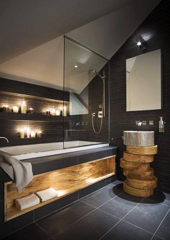 luxusbad schwarz mit rundem waschbecken, badewanne mit Glaswand und eingebautem holzregal zum badetücher organisieren und wandnischen für kerzendeko