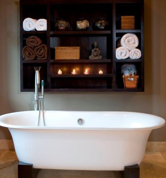 luxusbad mit kleiner badewanne freistehend und dunklem wandregal holz für dekoration und aufbewahrung von tüchern
