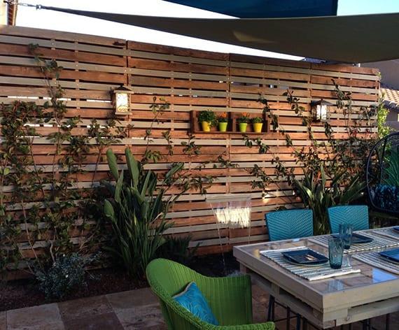 kreative gartengestaltung mit wand aus paletten, esstisch aus paletten mit grünen und blauen rattanstühlen und sonnensegel weiß