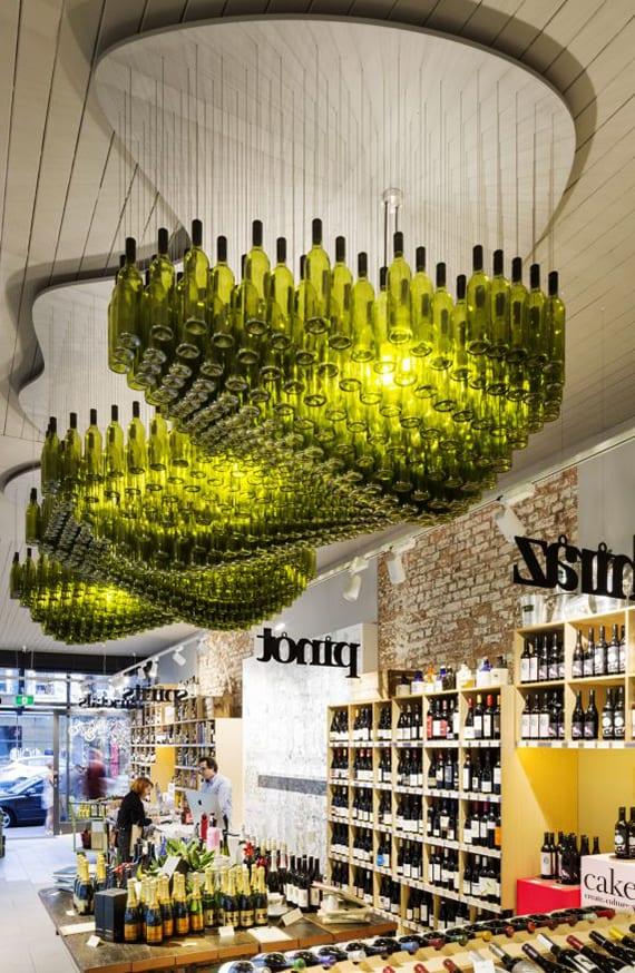 originelle deckengestaltung und lichtgestaltung mit moderner pendelleuchte aus grünen weinflaschen