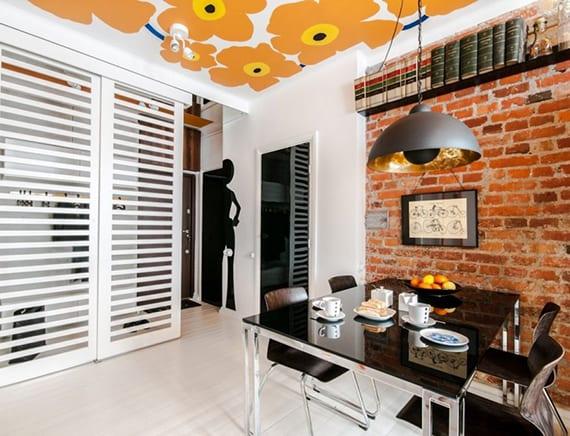 coole einrichtungsideen für altbauwohnung ohne eingangsbereich_stilvolle raumgestaltung in weiß mit ziegelwand und gemusterter decke mit orangen blumen