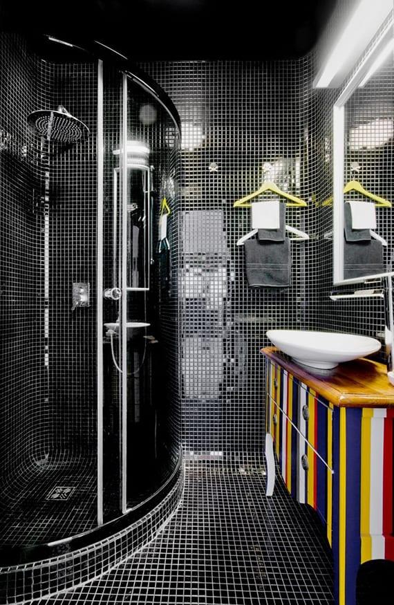 kleines luxusbad mit schwarzen mosaikfliesen, eckduschkabine, buntem waschtischschrank aus holz und farbigen kleiderbügeln als handtuchhalter