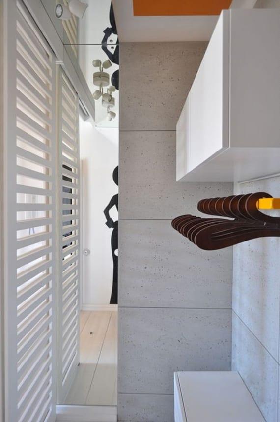 kleine begehbare Garderobe modern gestalten mit betonplatten, wandspiegel, wandregal weiß und kleiderstange gelb