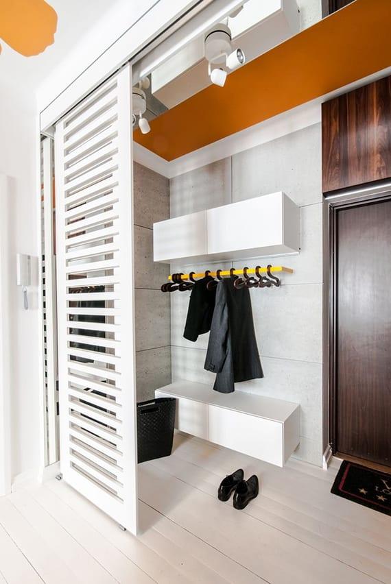 kreative wohnidee für kleine begehbare garderobe im eingangsbereich mit weißen schiebetüren und schuhregalen, oranger decke und deckenlichtwerfern