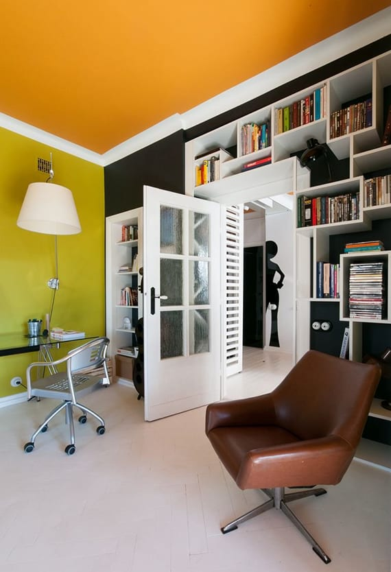 modernes wohnzimmer gestalten in grün, orange und schwarz mit weißen wandregalen, ledersessel braun und schreibtisch glas