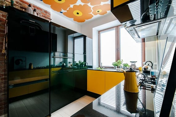 ideen für moderne küche mit schwarzen küchenschränken, schwarzer küchenarbeitsplatte über gelben unterschränken und ziegelwand