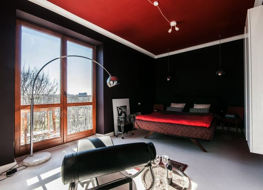 modernes farbkonzept schlafzimmer in dunkelbraun, rot und weiß_schlafzimmer einrichten mit stehlampe und kugel-pendellampen in silber, liegestuhl schwarz und retro-holzbettgestell