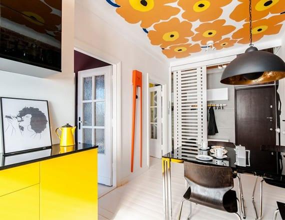 küche gestalten mit weißem holzboden, gelben küchenschränke und schwarzer arbeitsplatte, retro-tapete an der decke und schwarzer pendellampe über glasesstisch