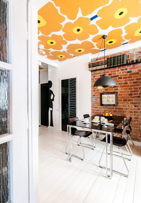 kreative gestaltung küche mit akzentwand aus roten ziegeln, schwarzen glastüren, retro-tapete mit orangen blumen und weißem holzboden