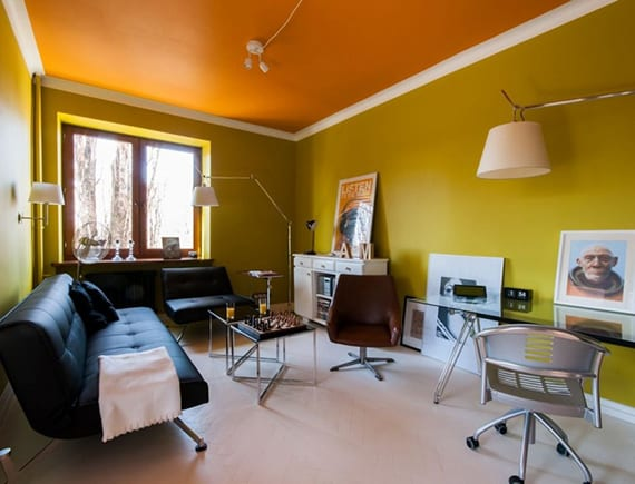 gestaltungsidee wohnzimmer mit wandfarbe olibegrün, oranger decke, weißem holzboden und modernen ledersofa und ledersessel schwarz