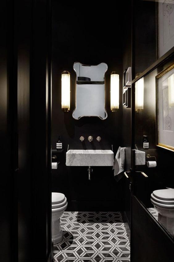 komplett schwarzes bad mit geometrisch gemusterten weißen bodenfliesen