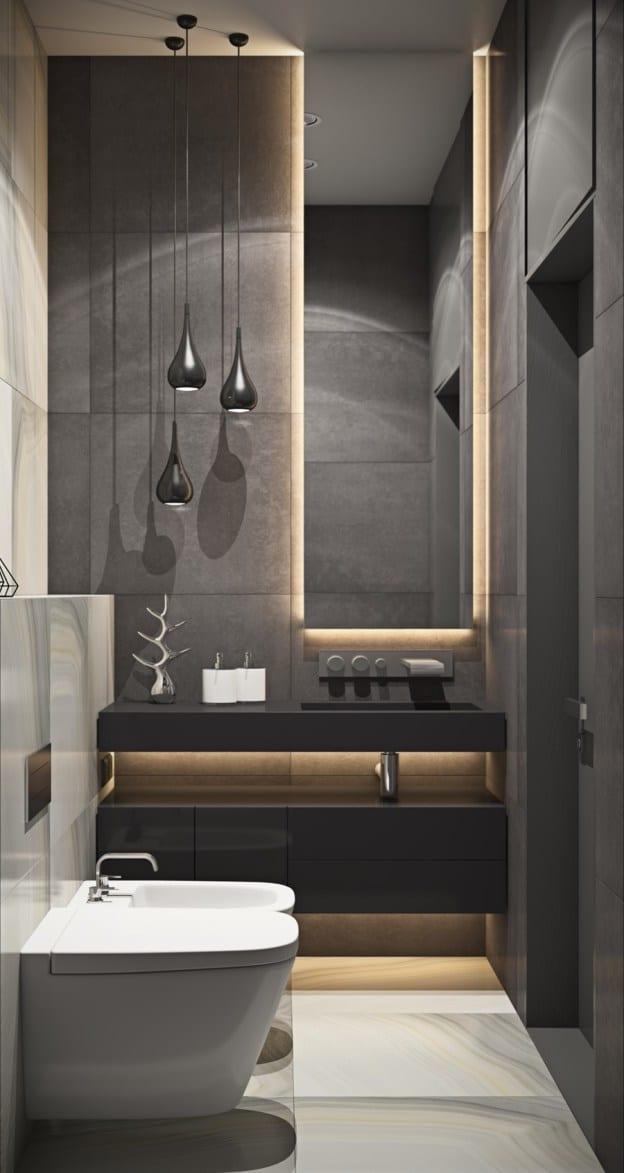 kleines luxusbad mit großen schwarzen und weißen badfliesen, indirekt beleuchtetem wandspiegel und modernen pendelleuchten schwarz über waschtischschrank in schwarzlack