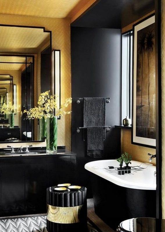 luxusbad schwarz mit goldenen tapete, wandspiegel in schwarzem metallrahmen und schwarze wandverkleidung um die freistehende badewanne