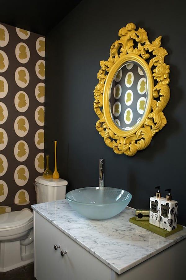 moderne und bunte badgestaltung mit tapete, wandfarbe schwarz, waschtisch mit marmorplatte weiß und wandspiegel mit gelbem spiegelrahmen