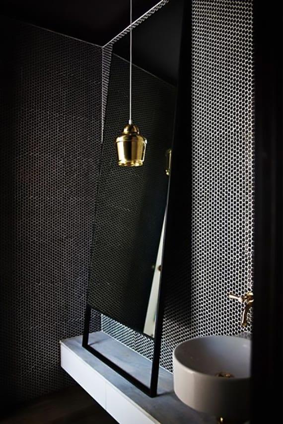 minimalistische badgestaltung mit badspiegel in schwarzem rahmen, weißem waschtisch mit rundem aufsatzwaschbecken, pendellampe gold und coole wandgestaltung mit modernen badfliesen schwarzweiß